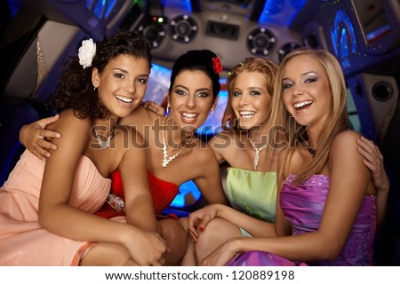 Beautiful young girls having party in limousine, smiling.