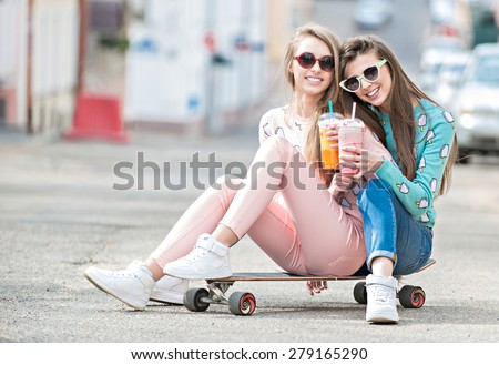 Beautiful young girls hipster girlfriends posing with a skateboard seat on skate, street fashion lifestyle in sunglasses. Keep cocktail and smiling - stock photo