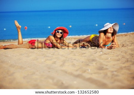 Beautiful young girls resting at the beach in hot summer - stock photo