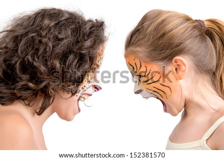 Beautiful young girls with feline painted faces, tiger and leopard - stock photo