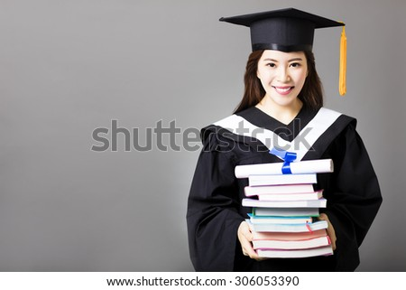 beautiful young  graduate holding diploma and book - stock photo