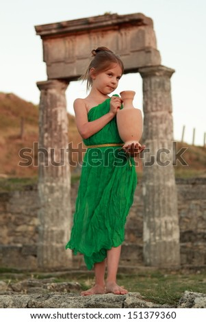 Beautiful young Greek goddess in emerald green vintage dress holding of an ancient amphora on the background of the ruins of the ancient city - stock photo