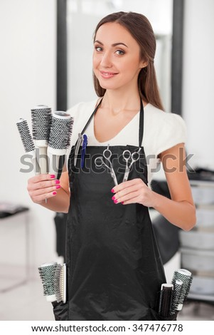 Beautiful young hairdresser is holding hairbrush and scissors. She is standing and smiling. The woman is looking at camera happily - stock photo