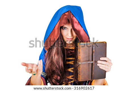 Beautiful young halloween witch wearing vintage gothic dress with hood holding magical book of spells in old leather cover isolated on white background