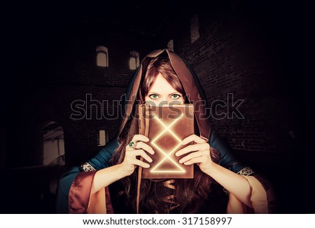 Beautiful young halloween witch wearing vintage gothic dress with hood holding magical book of spells in old leather cover inside ancient dark castle
