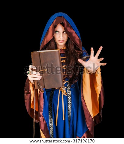 Beautiful young halloween witch wearing vintage gothic dress with hood holding magical book of spells in old leather cover making magic isolated on black background