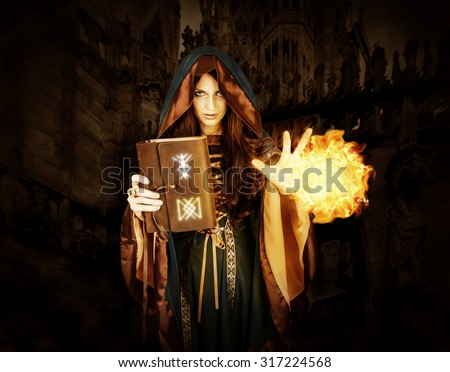 Beautiful young halloween witch wearing vintage gothic dress with hood holding magical book of spells in old leather cover with runes making fire ball magic in dark gothic castle
