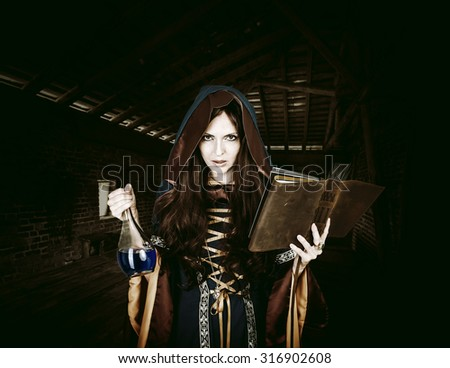 Beautiful young halloween witch wearing vintage gothic dress with hood reading magical book of spells in old leather cover and holding potion in night castle - stock photo