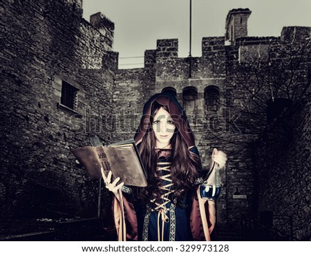 Beautiful young halloween witch wearing vintage gothic dress with hood reading magical book of spells in old leather cover - stock photo