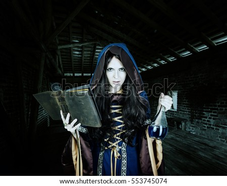 Beautiful young halloween witch wearing vintage gothic dress with hood reading magical book of spells in old leather cover and holding potion in glass flask in night castle
