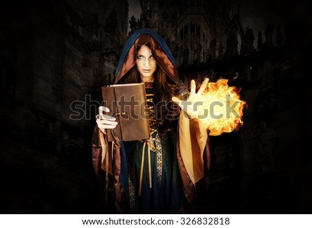 Beautiful young halloween witch wearing vintage gothic hood holding magical book of spells in old leather cover making fire ball magic near dark gothic castle - stock photo