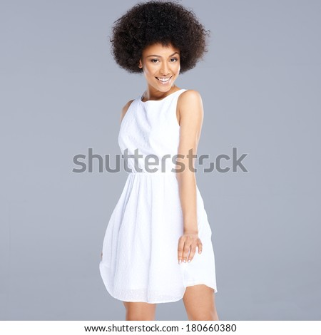 Beautiful young happy African American woman in a fresh short white dress smiling at the camera, square format on grey