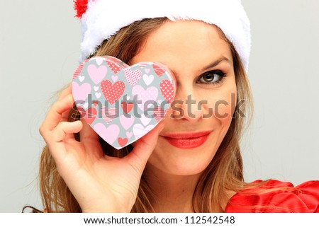 Beautiful Young Happy Christmas Woman holding a heart shaped gift box neutral background