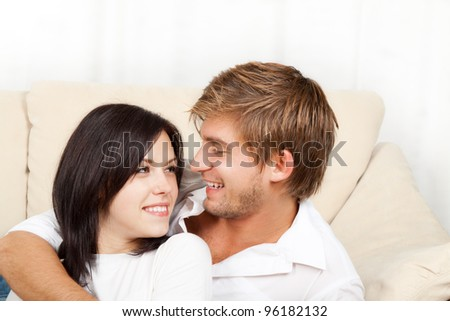 beautiful young happy couple  laying on couch happy smile looking to each other, portrait of lovely young man and woman hug, embrace on the sofa - stock photo