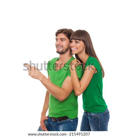 beautiful young happy couple love smiling embracing point finger to empty copy space, man and woman smile looking up wear green t shirt, isolated over white background