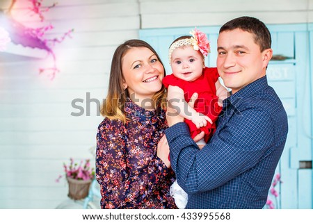 Beautiful young happy family with newborn baby daughter together on the background of a white house porch. Happy childhood. Background, macro, closeup - stock photo