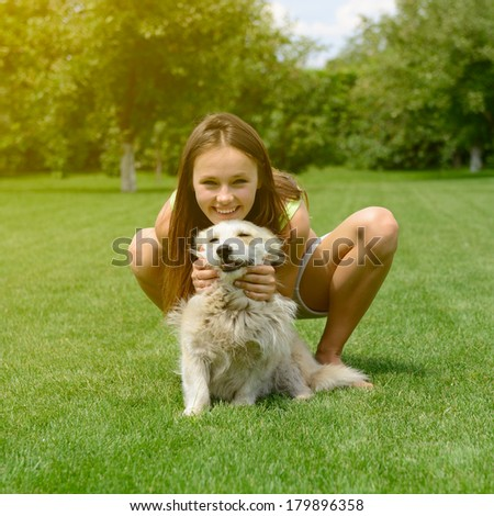 beautiful young happy laugh girl playing with her dog outdoor, toned - stock photo