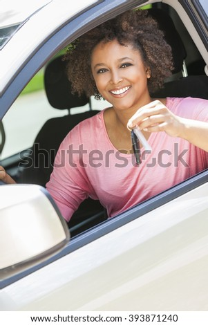 Beautiful young happy smiling mixed race black African American woman driving a car and holding the key - stock photo