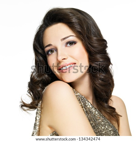Beautiful young happy smiling woman with brown curly hairs poses at studio - stock photo