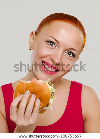 Beautiful young happy woman eating juicy burger and smiling