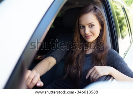 Beautiful young happy woman in car. Attractive  smiling caucasian girl sitting in white auto. pretty female person driving big car suv - stock photo
