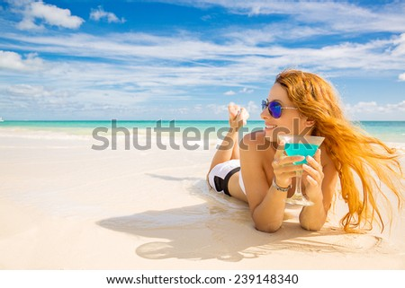 Beautiful young happy woman laying on the beach enjoying sunny weather looking on the ocean view. Tropical nature paradise getaway travel vacation tourism concept. Positive emotion face expression - stock photo