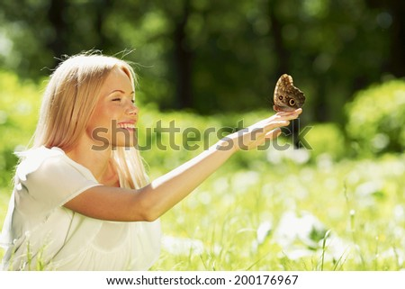 Beautiful young happy Woman playing with butterfly outdoors