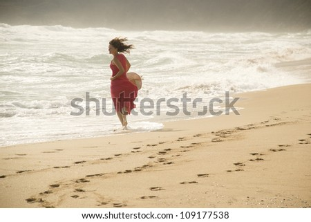 Beautiful young happy woman wearing red dress playing with the waves on a sandy beach - stock photo
