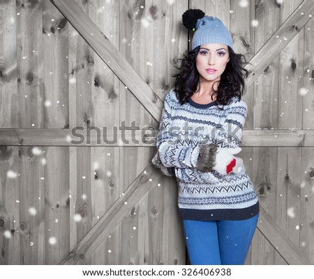 Beautiful  young happy  woman wearing winter hat and gloves covered with snow flakes. Christmas portrait concept.  - stock photo