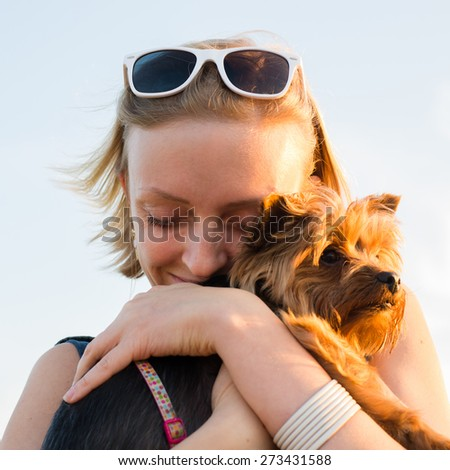 beautiful young happy woman with blonde hair, closing her eyes and holding small dog - stock photo