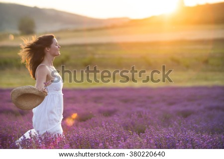 Beautiful young  healthy woman with a white dress running joyfully through a lavender field holding a straw hat under the rays of the setting sun. - stock photo