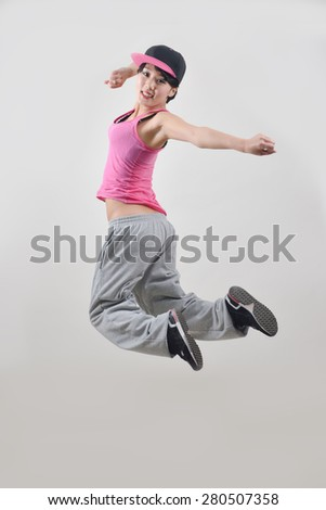 Beautiful young hip-hop dancer, jumping in the air - stock photo