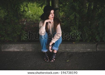 beautiful young hipster girl sitting in the park - stock photo