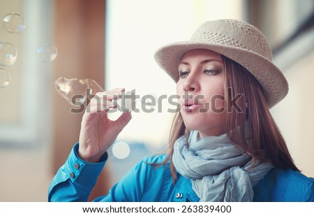 Beautiful young hipster woman in hat and blue jacket blowing bubbles - stock photo