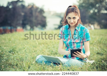 beautiful young hipster woman using laptop and tablet in the park