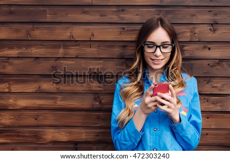 Beautiful young hipster woman using smart phone.