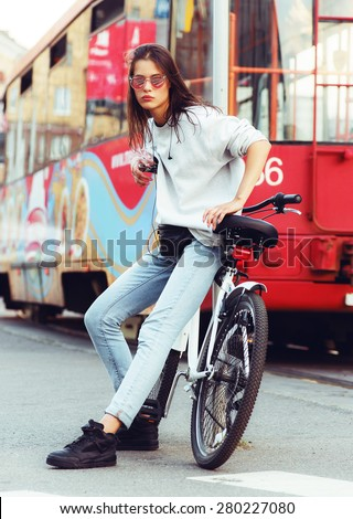 beautiful young hipster woman with bike in the city. Urban fashion lifestyle - stock photo