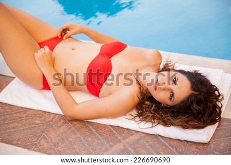 Beautiful young Hispanic brunette wearing a bikini and relaxing by a pool