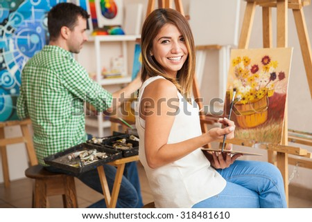 Beautiful young Hispanic woman and a handsome man attending a painting workshop together and having fun - stock photo