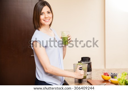 Beautiful young Hispanic woman drinking a glass freshly made healthy juice at home - stock photo