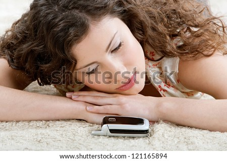 Beautiful young hispanic woman laying down on a furry carpet at home, looking at her cell phone and patiently waiting for a phone call.