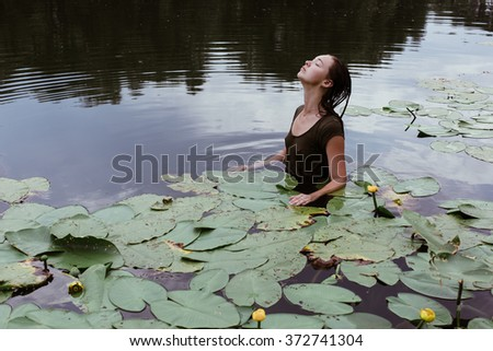 beautiful young hot model girl swimming in the lake full of water lilies during hot summer day - stock photo