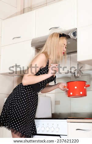Beautiful young housewife in the kitchen. A girl holding a pot.