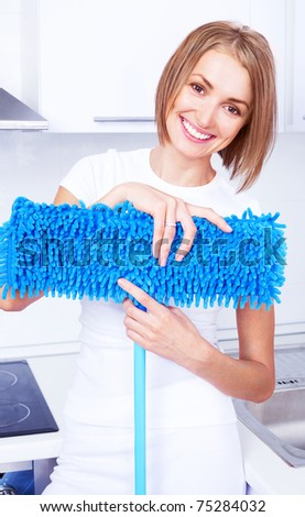 beautiful young housewife with a mop in the kitchen - stock photo