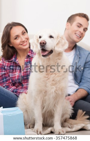 Beautiful young husband and wife are sitting on floor near their puppy. They are looking at camera and smiling - stock photo