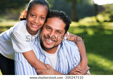 beautiful young indian girl with her father outdoors - stock photo