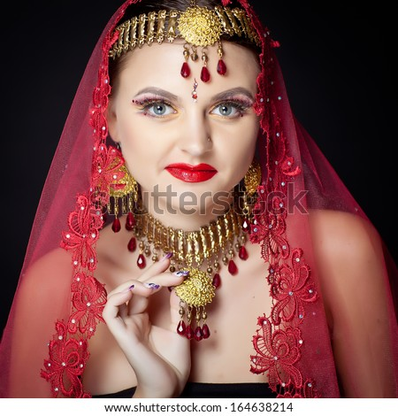 Beautiful young indian woman bellydancer n traditional clothing with bridal makeup and jewelry. gorgeous brunette bride traditionally dressed  India.