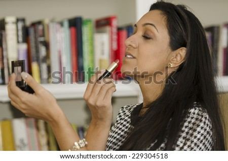 Beautiful young Indian woman checking your makeup in the mirror - stock photo