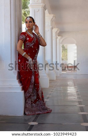 Beautiful Young Indian Woman in Red bridal Sari clothing with bridal oriental jewelry. Beautiful Indian Girl in Wedding Sari. Indian Bride in the Temple