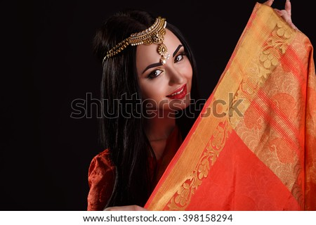 Beautiful Young Indian Woman in red Traditional Clothing with perfect Makeup and Oriental Jewelry. Beautiful Girl Bollywood dancer (Bellydancer) in Sari. Eastern fairy tale - stock photo